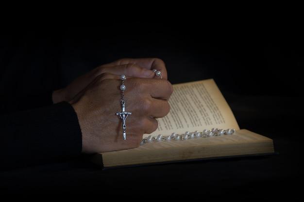 Руки, возносящие католический розарий. жесты вера слава богу