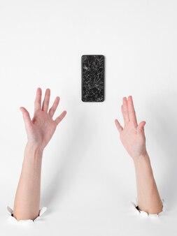壊れたスマートフォンで穴を通す手