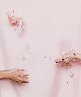 Hands throwing petals with textile background