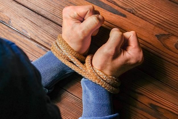 손은 나무 배경에 생명을 위협하는 밧줄로 묶여 있습니다.