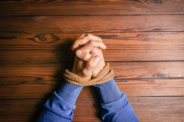 Hands tied with a rope life-threatening on a wooden background.