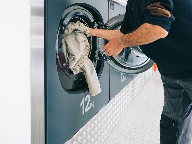 Руки загружают белье в стиральную машину в химчистку. концепция очистки