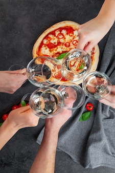 Hands together with glasses of white wine on background pizza