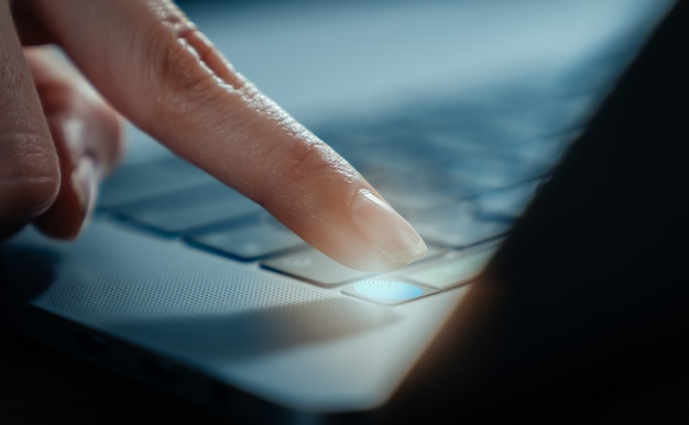 Hands touch fingerprint on the laptop screen scanner to access personal user online.