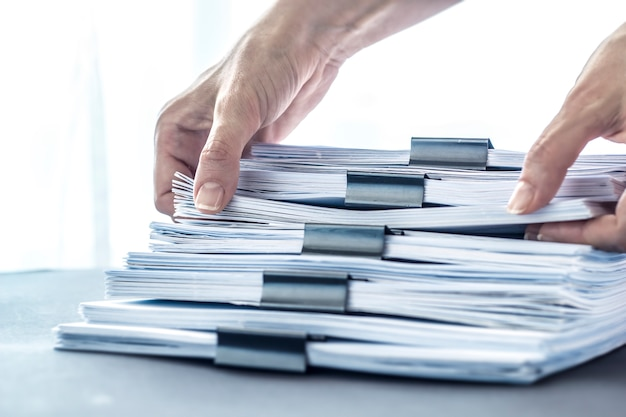 Hands touching office paper. stacks documents files with black clip.