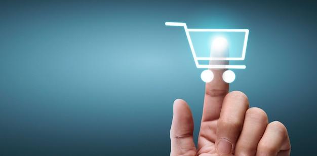 青の背景にショッピング カート ボタン デジタル デザインに触れる手