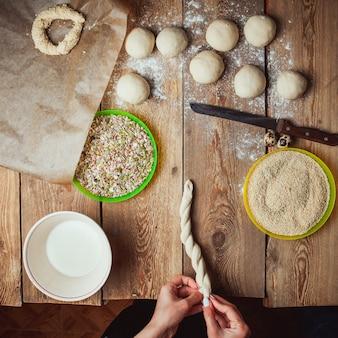 Руки скручивают тесто, чтобы приготовить турецкий бублик симит вид сверху.