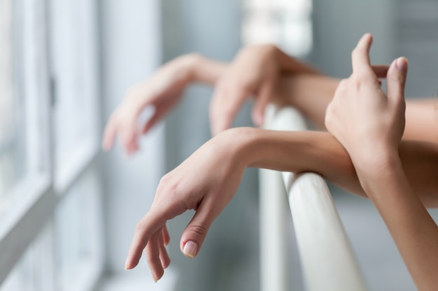 Hands of two classic ballet dancers at barre