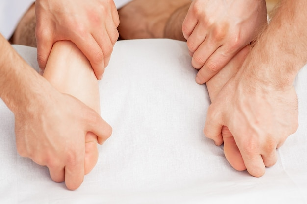 Hands of two massagers are giving massage to soft bare feet during spa foot treatment.