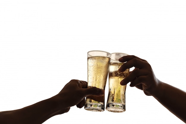 The hands of two men holding a glass of beer raised together to drink to celebrate the success.