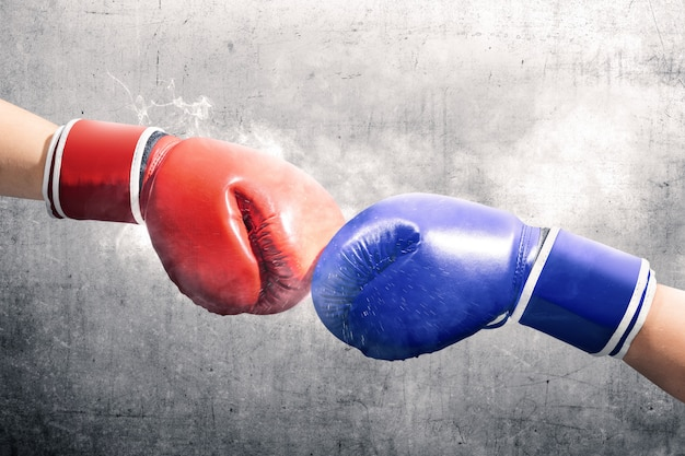 Hands of two men with blue and red boxing gloves bumped their fists