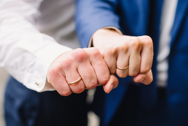 Hands of two men with wedding gold rings