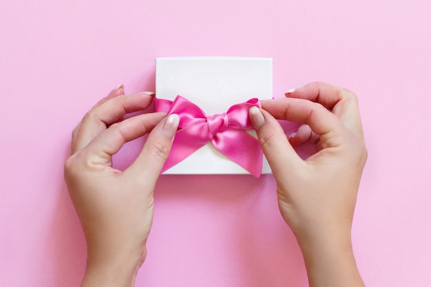 Hands tying a bow on a white gift box  on a light pink background close up