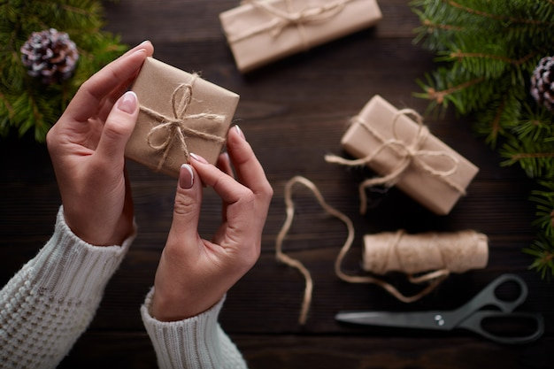Hands tying the knot of string of gift packages