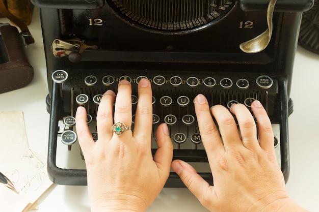 Hands typing on black vintage typewriter