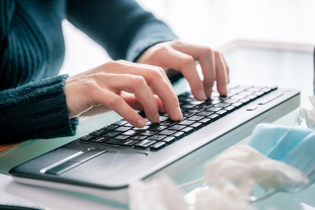 病気を示すテーブルの上のマスクとハンカチで在宅勤務中にコンピューターを入力する手