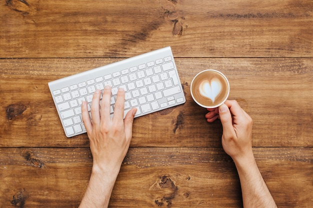 Hands typing on keyboard and holding coffee