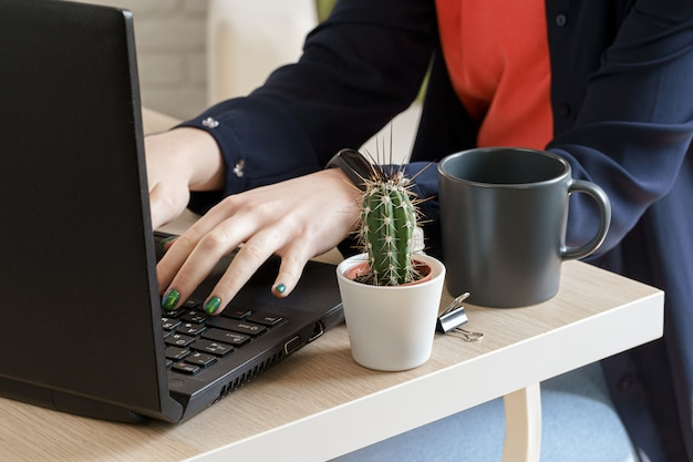 Hands typing on laptop keyboard in an office