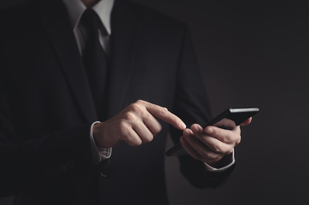 Руки, набрав сообщение на смартфоне. красивый бизнесмен в черном костюме.