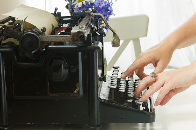 黒のビンテージタイプライターで入力する手がクローズアップ