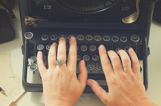 黒のビンテージタイプライターでタイプする手