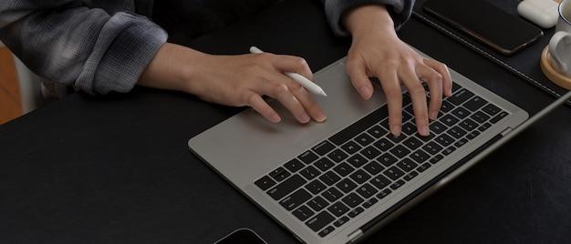 オフィスの机の上のノートパソコンのキーボードで入力する手
