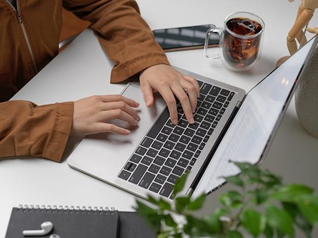スマートフォン、消耗品、装飾を備えたノートパソコンのキーボードで入力する手