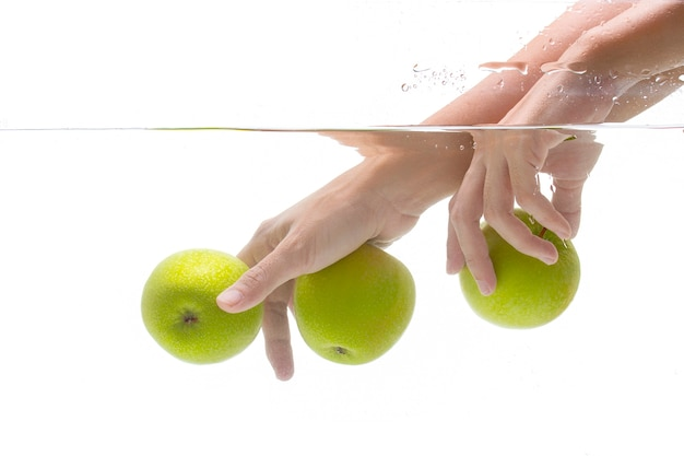 Hands in underwater with green apple on white background.