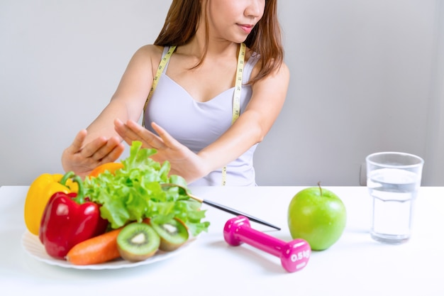 Hands of unhappy asian woman push out vegetables and fruits with bored emotion on dieting time