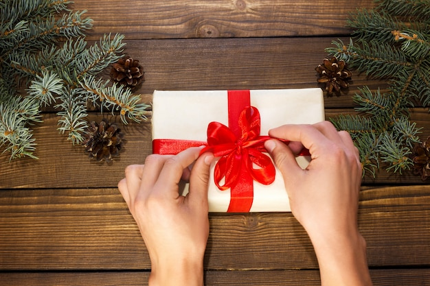 Hands unpack christmas gift on a wooden background with fir branches and cones