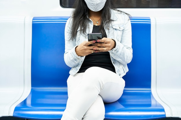 Hands of an unrecognizable black woman sitting in the subway car using a smartphone.