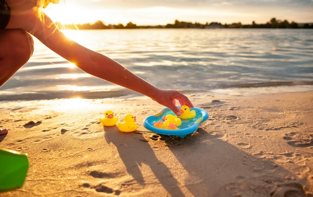 Hands of unrecognizable caucasian child playing with rubber yellow ducks in small blue pool and sitting on seashore