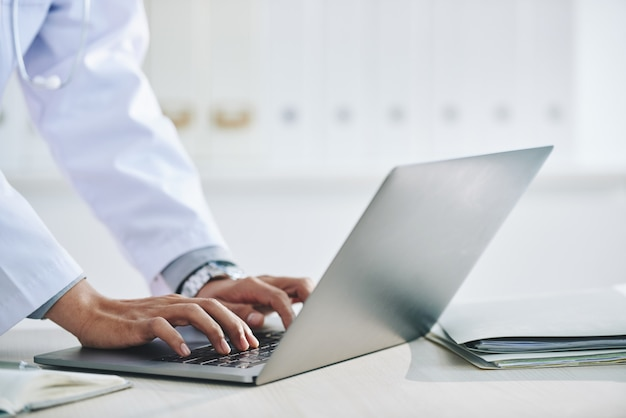 Hands of unrecognizable female doctor using laptop in office