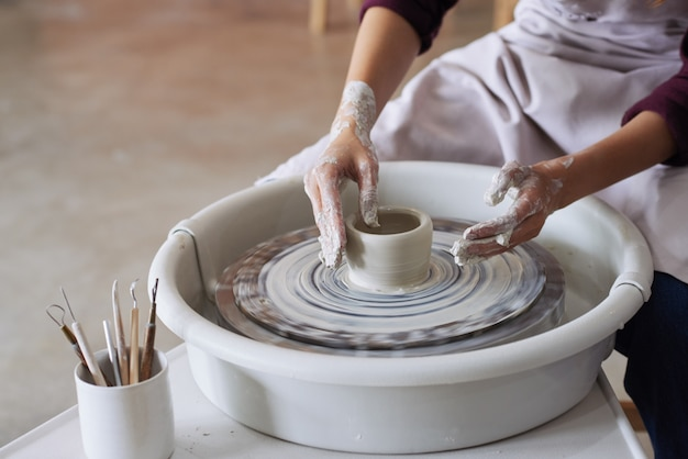 Hands of unrecognizable female potter making clay vessel on pottery wheel