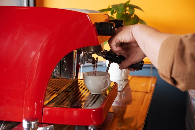 Hands of unrecognizable man brewing cup of coffee on espresso machine