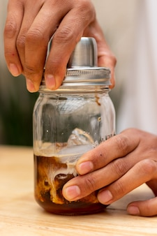 The hands of an unrecognizable man closing a beverage shaker filled with liquor and milk with ice