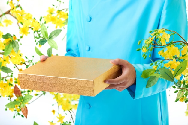 Hands of unrecognizable man in traditional jacket posing with blooming mimosa and square box
