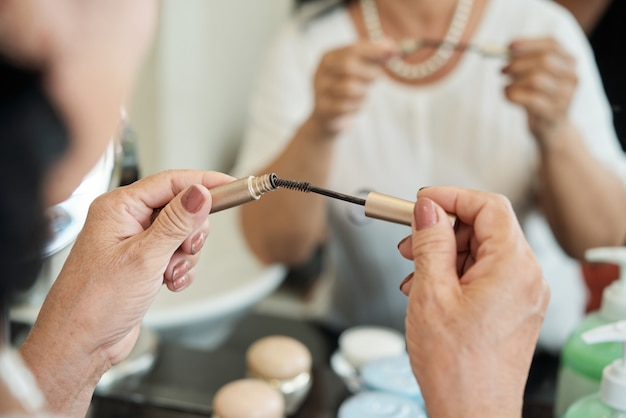 Hands of unrecognizable senior lady holding mascara in front of mirror