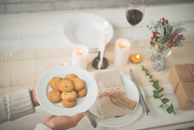 Hands of unrecognizable woman putting plate of biscuits on lovely christmas table