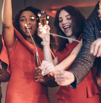Hands up and partying. multiracial friends celebrate new year and holding bengal lights and glasses with drink