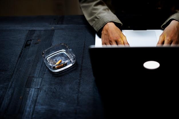 灰皿の中にタバコを置いたノートパソコンを使用している手