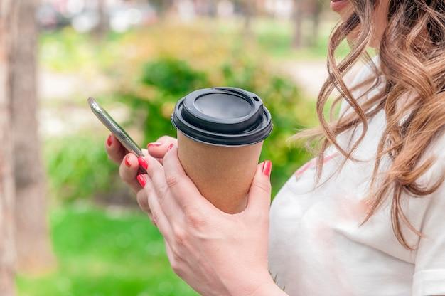 스마트 폰 앱에서 전화 문자 메시지를 사용하고 커피 잔을 들고 손
