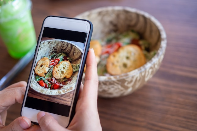 Руки с помощью телефона, чтобы сфотографировать еду