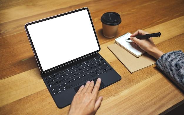 Руки, используя и касаясь сенсорной панели планшета с пустым белым экраном рабочего стола как компьютерный компьютер во время записи и работы, чашка кофе на деревянный стол
