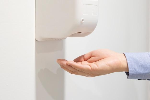 自動アルコールディスペンサーを使用して洗浄する手