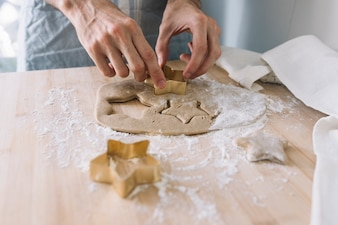 Hands using cookie cutter on dough
