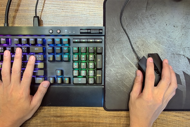 Hands using a keyboard with lights and mouse