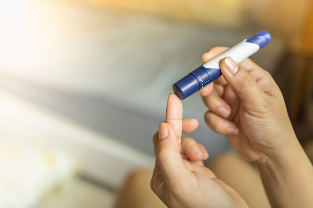 Hands using lancet on finger to check blood sugar level by glucose meter in the morning