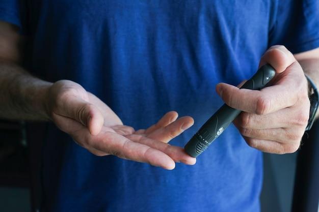 Руки с помощью ланцета на пальце в домашних условиях для проверки уровня сахара в крови