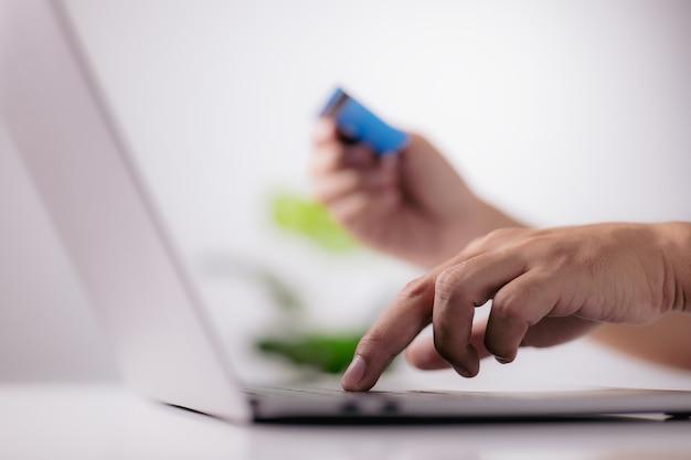 Руки с помощью ноутбука и кредитной карты. концепция покупок в интернете.